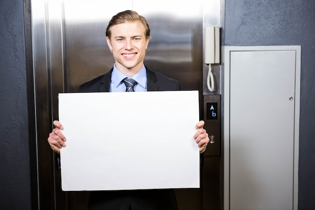 Portrait, de, homme affaires, tenue, a, enseigne, près, ascenseur