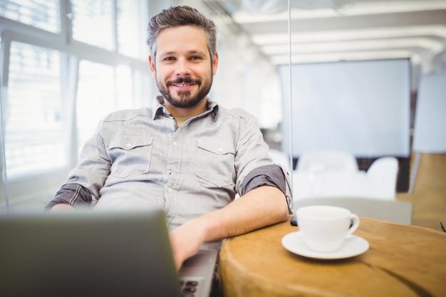 Portrait, homme affaires, utilisation, ordinateur portable, bureau