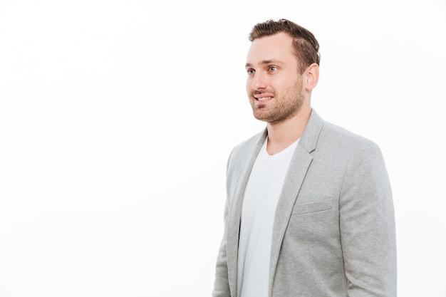 Portrait d'un homme d'affaires en veste ayant des poils posant avec le sourire et en regardant de côté, isolé sur l'espace de copie de mur blanc