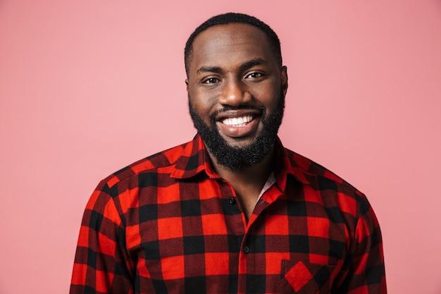 Portrait d'un homme africain heureux portant une chemise à carreaux debout isolé sur un mur rose