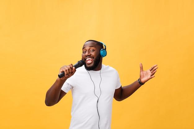 Portrait d'un homme africain joyeux tenant un microphone et ayant des écouteurs sur la tête, écouter de la musique chantant