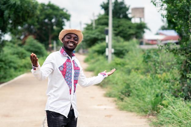 Portrait d'un homme africain portant un tissu natif traditionnel coloré avec sourire et heureux.