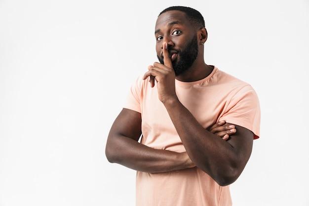 Portrait d'un homme africain sérieux portant un t-shirt debout isolé sur un mur blanc, montrant un geste de silence