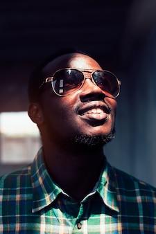 Portrait d'homme africain souriant barbu, portant des lunettes de soleil. style de clé faible