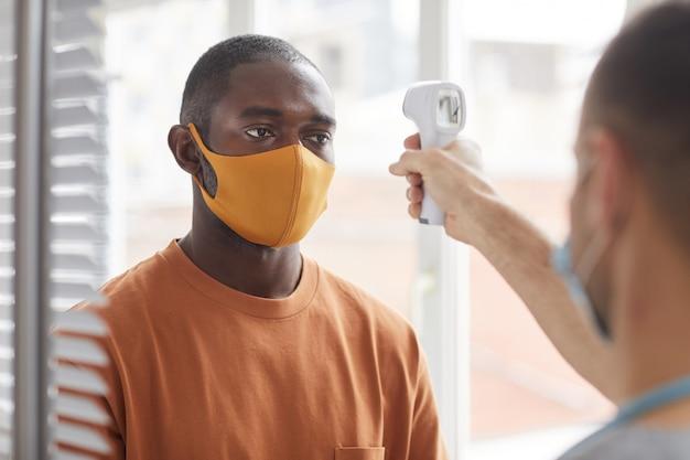 Portrait d'un homme afro-américain adulte portant un masque faisant la vérification de la température en faisant la queue à la clinique