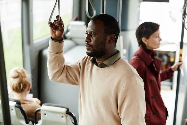 Portrait d'un homme afro-américain adulte tenant une balustrade dans un bus lors d'un voyage en transports en commun en ville, espace pour copie
