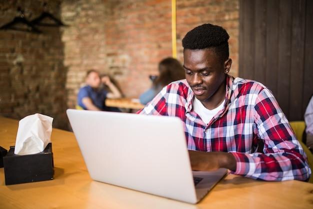 Portrait d'un homme afro-américain assis dans un café et travaillant sur un ordinateur portable.