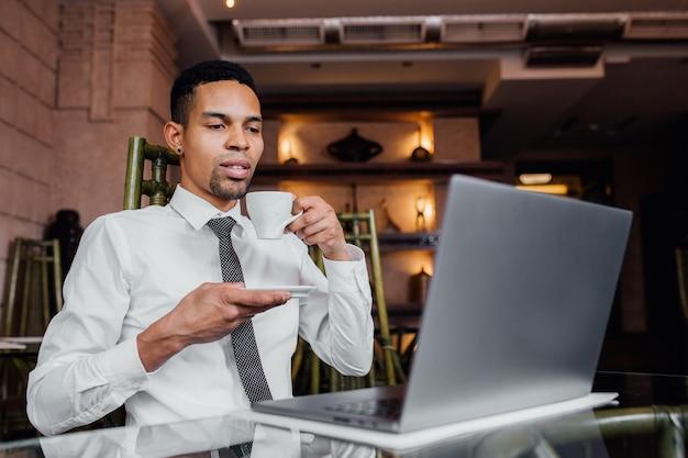 Portrait d'un homme afro-américain boire du café et travailler sur un ordinateur portable, dans une chemise blanche, à l'intérieur