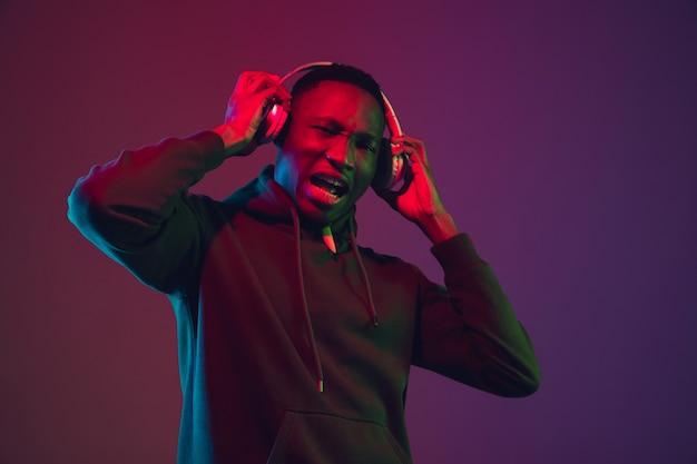 Portrait d'un homme afro-américain avec un casque sur fond de studio dégradé à la lumière du néon. beau modèle masculin chantant, dansant. concept d'émotions humaines, expression faciale, ventes, publicité, inclusion.