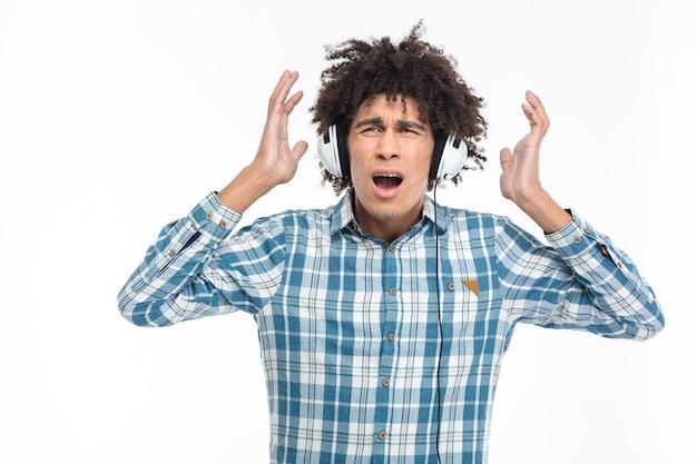 Portrait d'un homme afro-américain choqué dans des écouteurs écoutant de la musique isolée sur un mur blanc