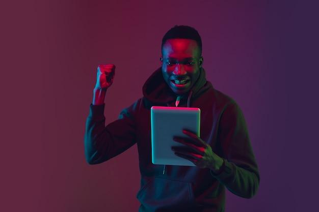Portrait de l'homme afro-américain choqué sur fond de studio dégradé à la lumière du néon