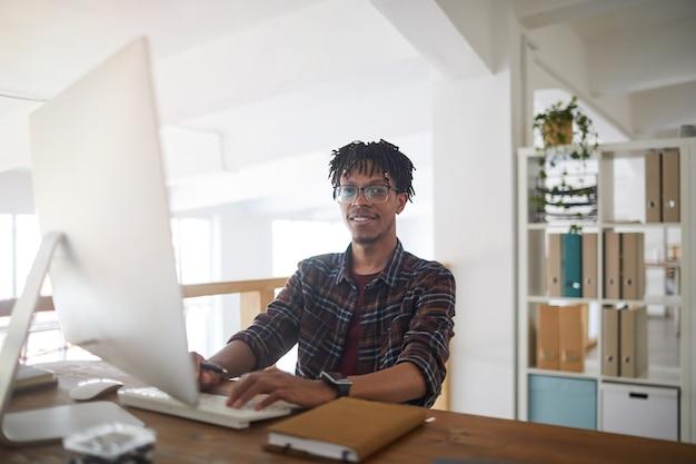 Portrait d'un homme afro-américain contemporain souriant à la caméra tout en utilisant un ordinateur et en tapant sur le clavier au bureau blanc, concept de développeur informatique, espace de copie
