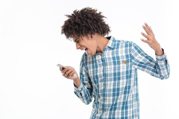 Portrait d'un homme afro-américain criant sur un smartphone isolé sur un mur blanc