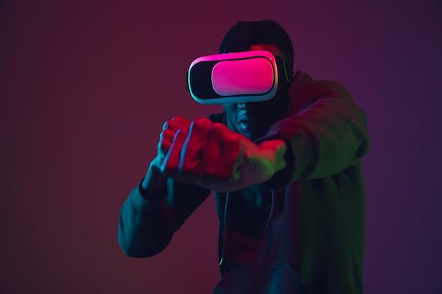 Portrait d'un homme afro-américain dans un casque vr isolé sur fond de studio dégradé à la lumière du néon. beau modèle masculin. concept d'émotions humaines, expression faciale, ventes, publicité, inclusion, technologie.