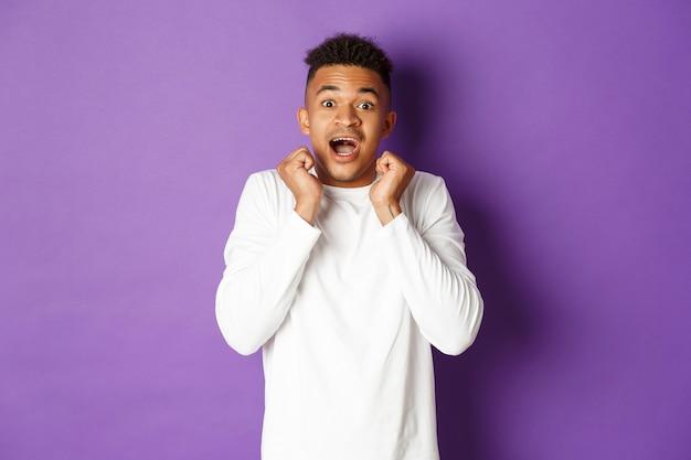 Portrait d'un homme afro-américain étonné en chemise décontractée blanche avec la bouche ouverte