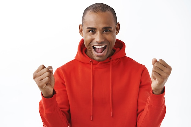 Portrait d'un homme afro-américain excité et enthousiaste en sweat à capuche rouge, serrant les poings en triomphe, remportant un prix, dites oui ou hourra