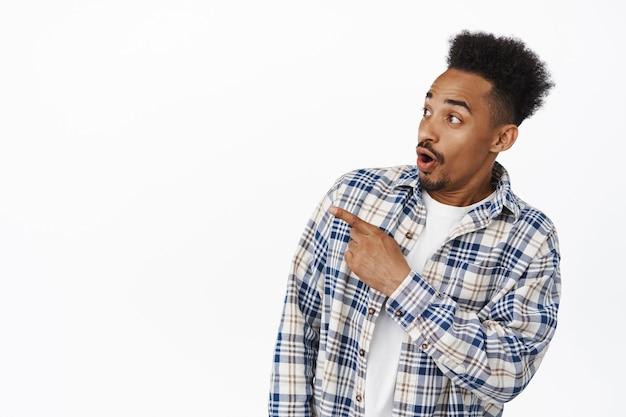 Portrait d'un homme afro-américain haletant, dites wow, pointant et regardant à gauche sur la promo surprise de la vente, vérifiant la nouvelle offre de remise, debout sur blanc