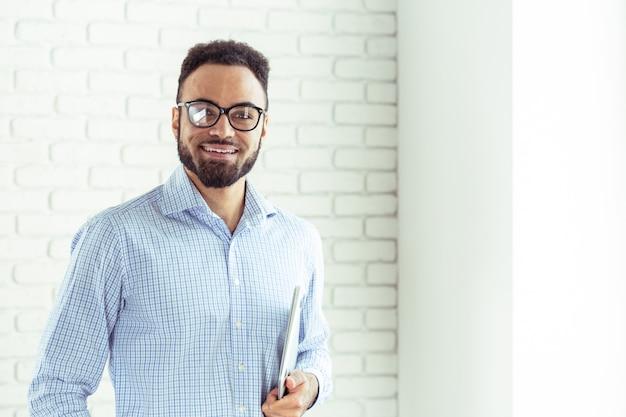 Portrait d'un homme afro-américain heureux à l'aide d'un ordinateur portable