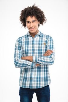 Portrait d'un homme afro-américain heureux debout avec les bras croisés et regardant isolé sur un mur blanc