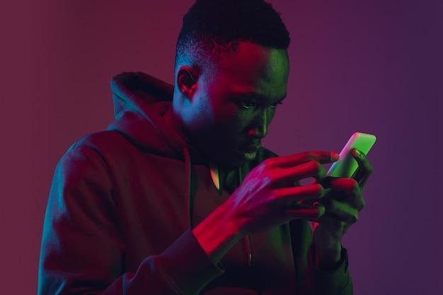 Portrait d'homme afro-américain isolé sur mur dégradé en néon