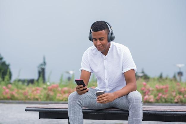 Portrait d'un homme afro-américain jeune et heureux avec des écouteurs. un homme assis sur un banc et écoutant de la musique, tenant un smartphone et une tasse de café