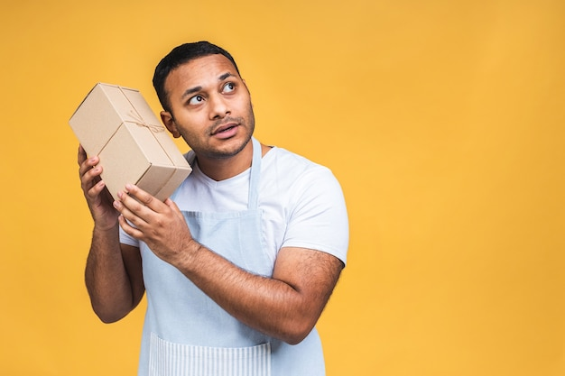 Portrait d'un homme afro-américain noir indien attrayant positif en tablier regardant la caméra isolée sur fond jaune. paquet de maintien.