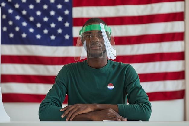 Portrait d'un homme afro-américain portant un masque de protection assis à la table et votant pour le drapeau américain