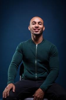 Portrait d'un homme afro-américain souriant sur bleu foncé