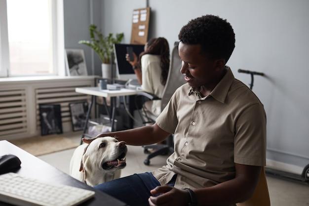 Portrait d'un homme afro-américain souriant caressant un chien tout en travaillant au bureau, espace de travail adapté aux animaux de compagnie