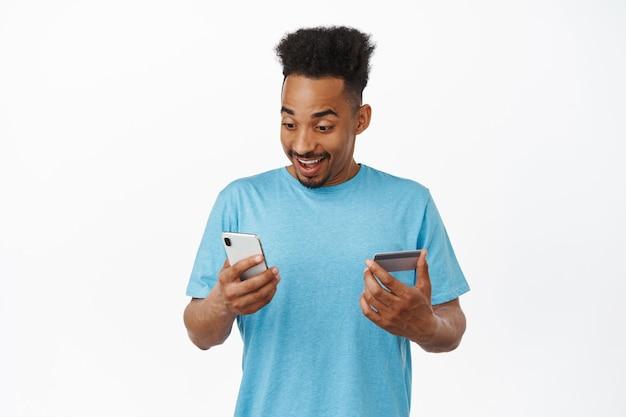 Portrait d'un homme afro-américain souriant utilisant un smartphone et une carte de crédit, payant en ligne, faisant des achats sur demande, debout en t-shirt bleu sur blanc