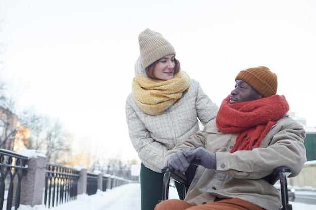 Portrait d'un homme afro-américain utilisant un fauteuil roulant à l'extérieur en hiver avec une jeune femme souriante le regardant et l'aidant, espace de copie