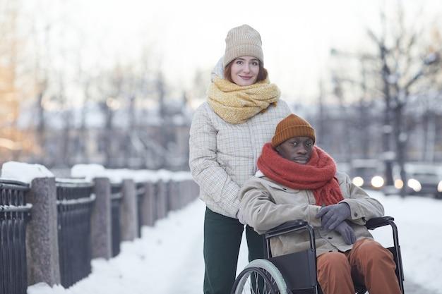 Portrait d'un homme afro-américain utilisant un fauteuil roulant regardant la caméra tout en posant à l'extérieur en hiver avec une jeune femme souriante aidant, espace de copie