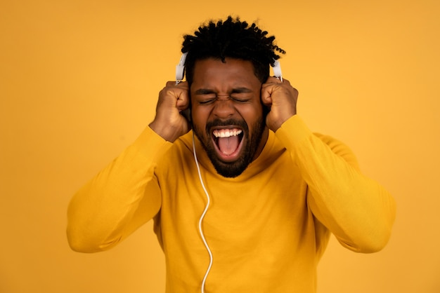 Portrait d'un homme afro appréciant écouter de la musique avec des écouteurs tout en se tenant sur un fond jaune isolé.