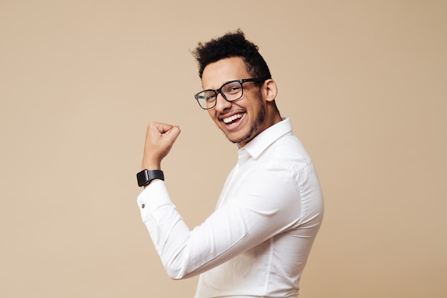 Portrait d'un homme afro excité debout avec les mains levées et regardant l'avant isolé sur un mur beige célébrant le succès