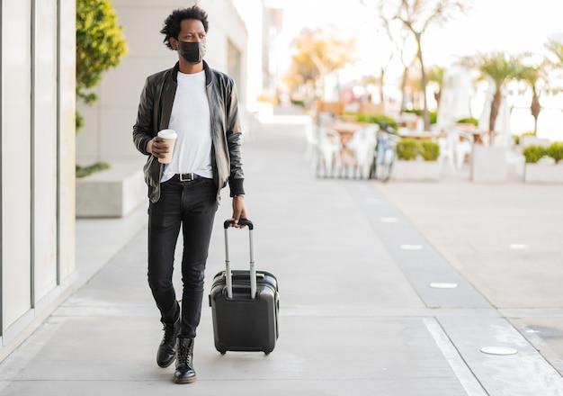 Portrait d'un homme afro-touriste portant valise et tenant une tasse de café en marchant à l'extérieur dans la rue. concept de tourisme.