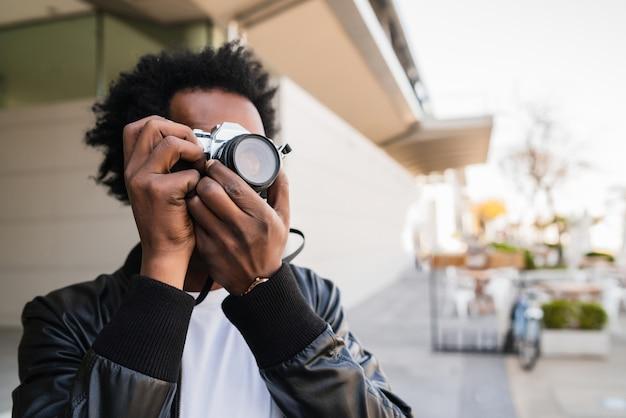 Portrait d'un homme afro-touriste à prendre des photos avec appareil photo en marchant à l'extérieur dans la rue