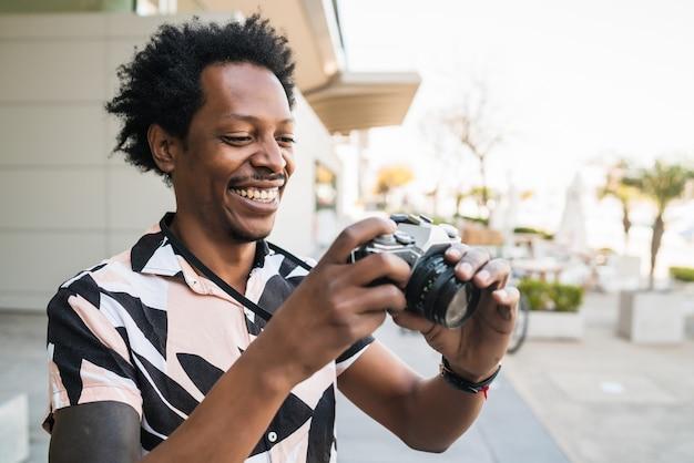 Portrait d'un homme afro-touriste à prendre des photos avec appareil photo tout en marchant à l'extérieur dans la rue. concept de tourisme.