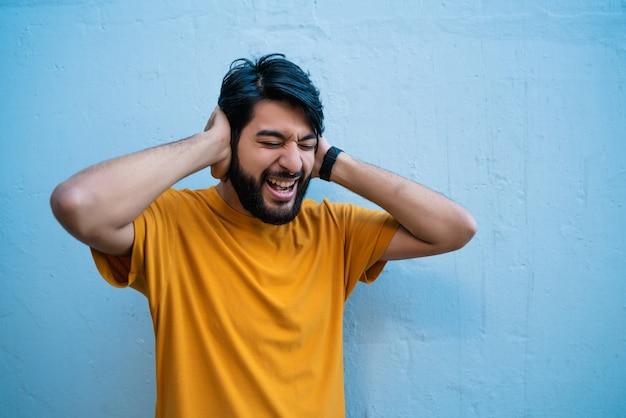 Portrait d'homme agacé et stressé couvrant ses oreilles avec les mains. fond bleu isolé.