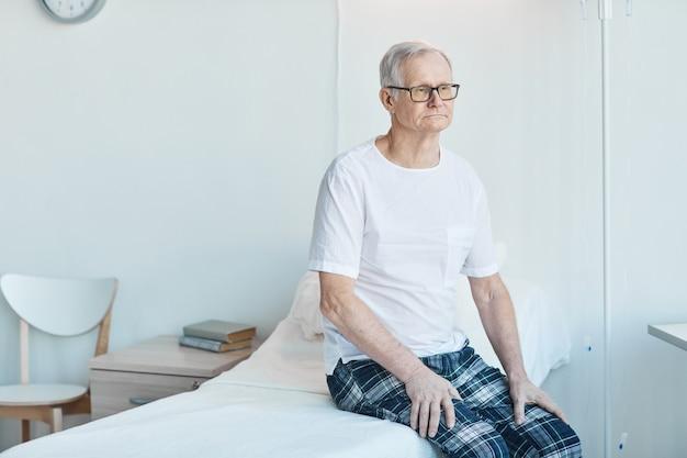 Portrait d'un homme âgé assis sur un lit d'hôpital dans une salle blanche et regardant loin pensivement, espace pour copie