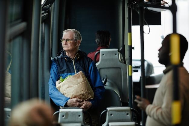 Portrait d'un homme âgé aux cheveux blancs regardant la fenêtre dans un bus lors d'un voyage en transports en commun en ville, espace pour copie