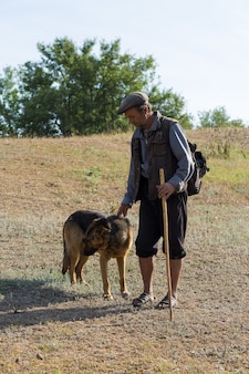 Portrait d'un homme âgé avec un chien de berger tôt le matin