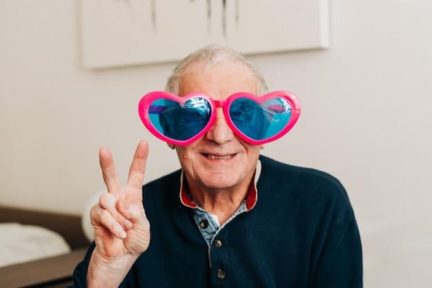 Portrait d'homme âgé heureux avec des lunettes en forme de coeur à la maison, concept d'amour