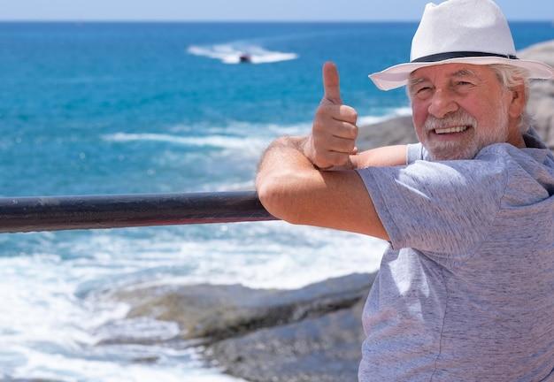 Portrait d'un homme âgé insouciant en vacances à la mer, regardant la caméra et souriant avec le pouce vers le haut. beau retraité profitant de la détente