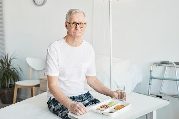 Portrait d'un homme âgé mangeant de la nourriture dans une chambre d'hôpital et regardant la caméra, espace de copie