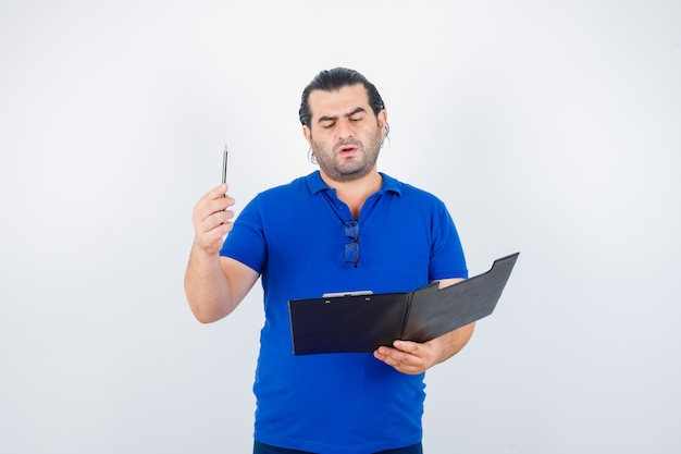 Portrait d'un homme d'âge moyen regardant à travers le presse-papiers tout en tenant un crayon en t-shirt polo et à la vue de face réfléchie