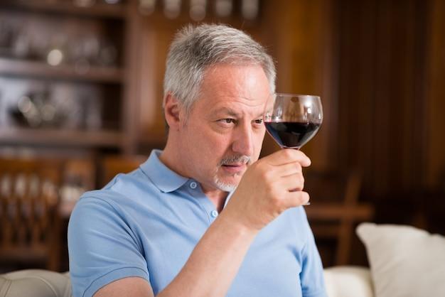 Portrait d'un homme d'âge mûr en dégustant un verre de vin rouge à la maison