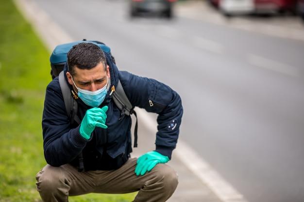 Portrait d'un homme d'âge mûr avec un masque facial médical se trouve dans la rue de la ville.
