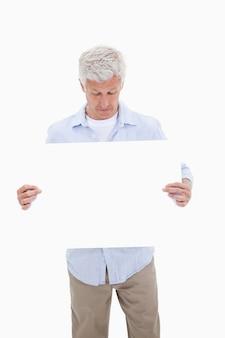 Portrait d'un homme d'âge mûr en regardant un panneau vierge