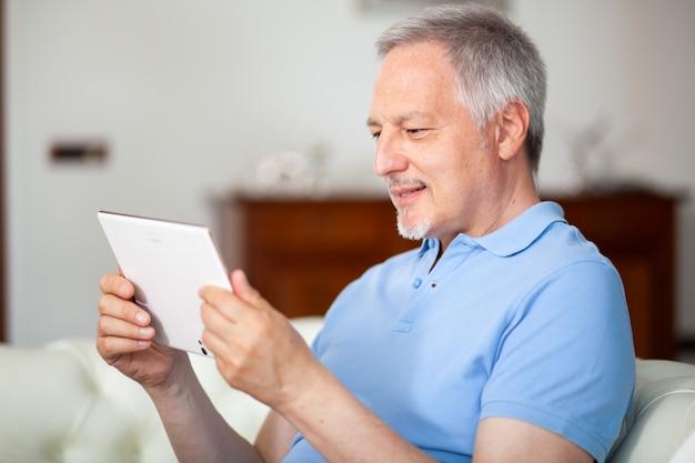 Portrait d'un homme d'âge mûr souriant à l'aide de sa tablette numérique tout en étant assis sur le canapé