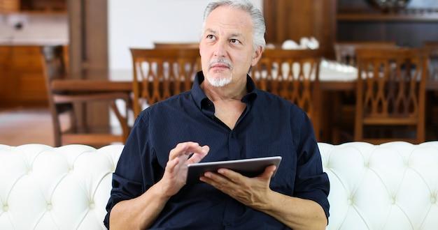 Portrait d'un homme d'âge mûr souriant à l'aide de sa tablette numérique tout en restant assis sur le canapé